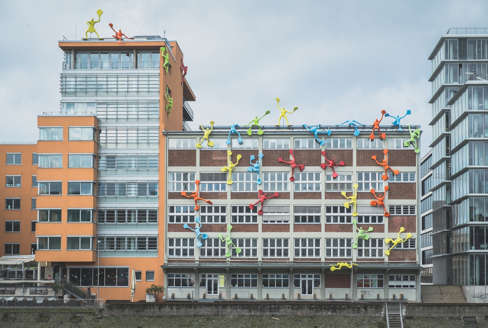 Bright colored plastic sculptures climb the facade.