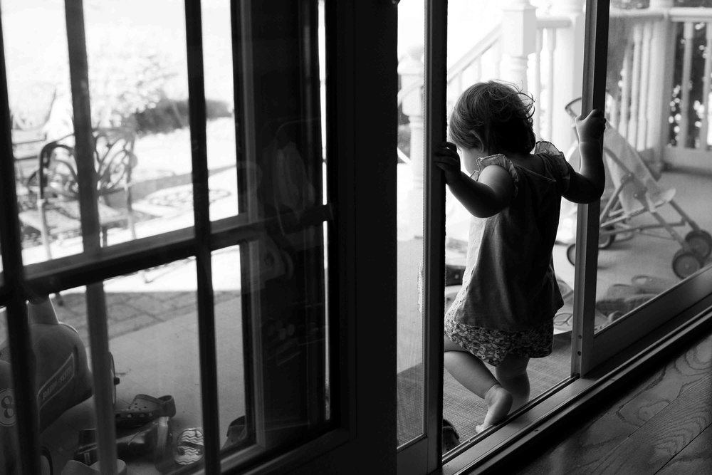 little girl going outside through a doorway