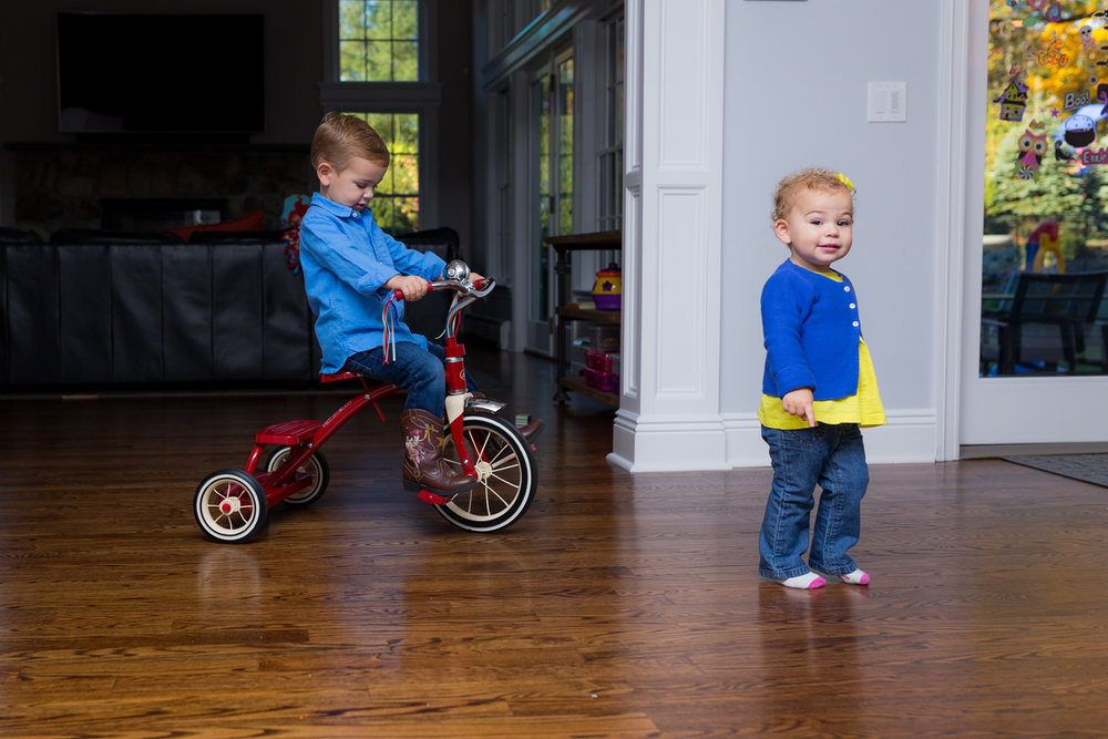 riding a radio flyer tricycle inside the house