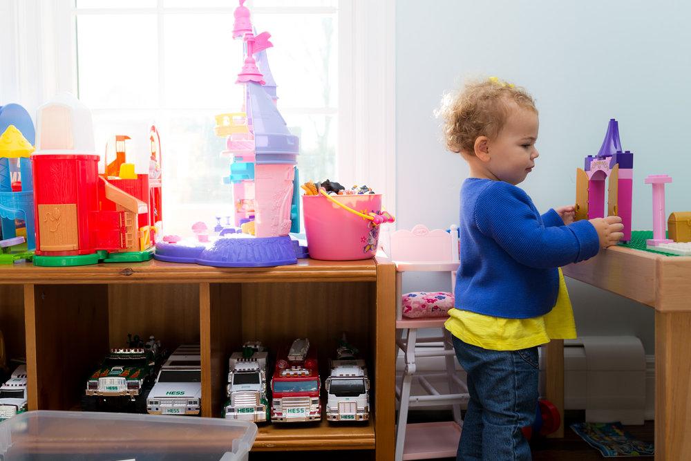 baby girl looking at sister's legos