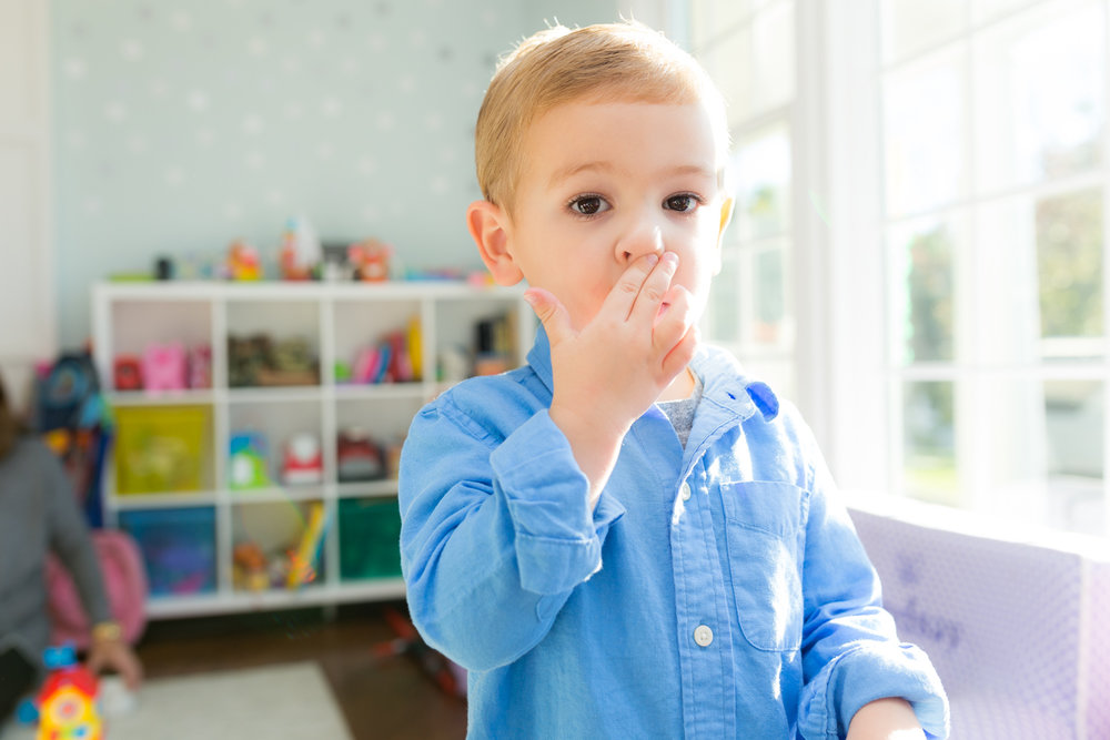 little boy wiping his nose