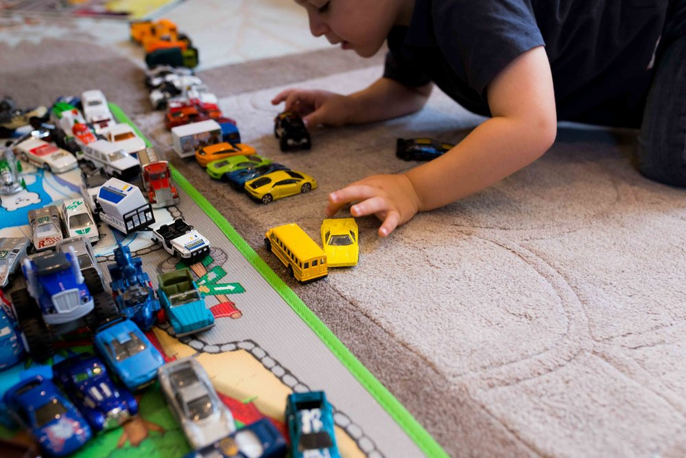 toddler playing with matchbox cars