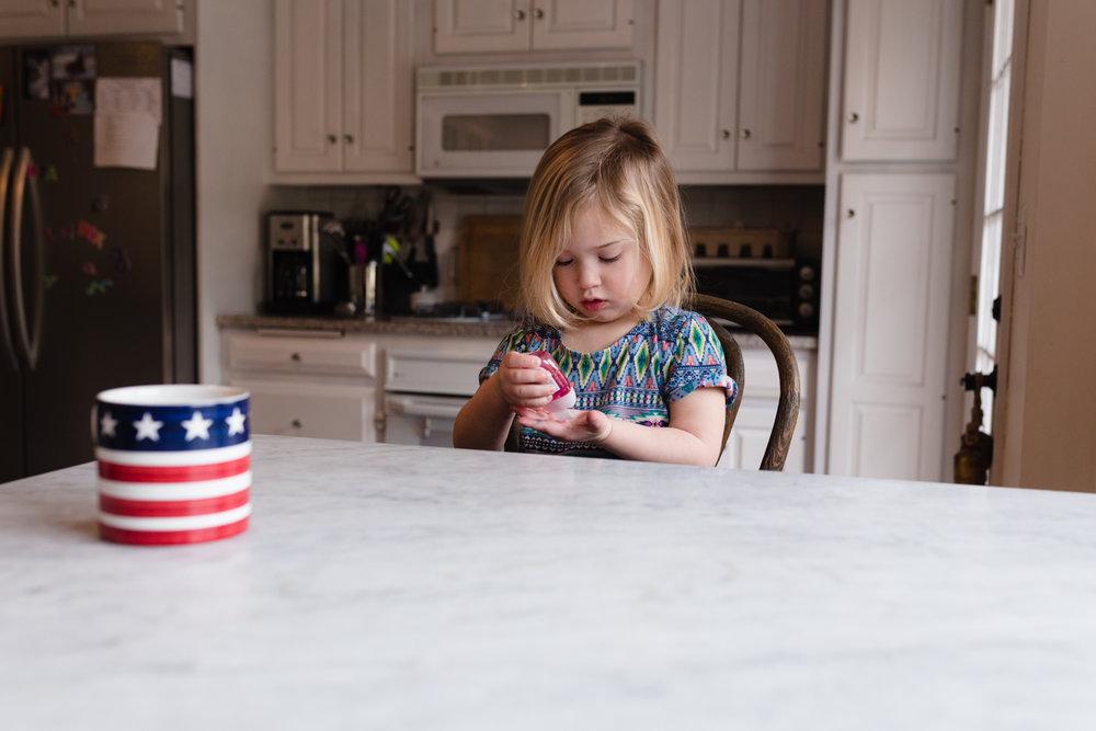 little girl using hand sanitizer