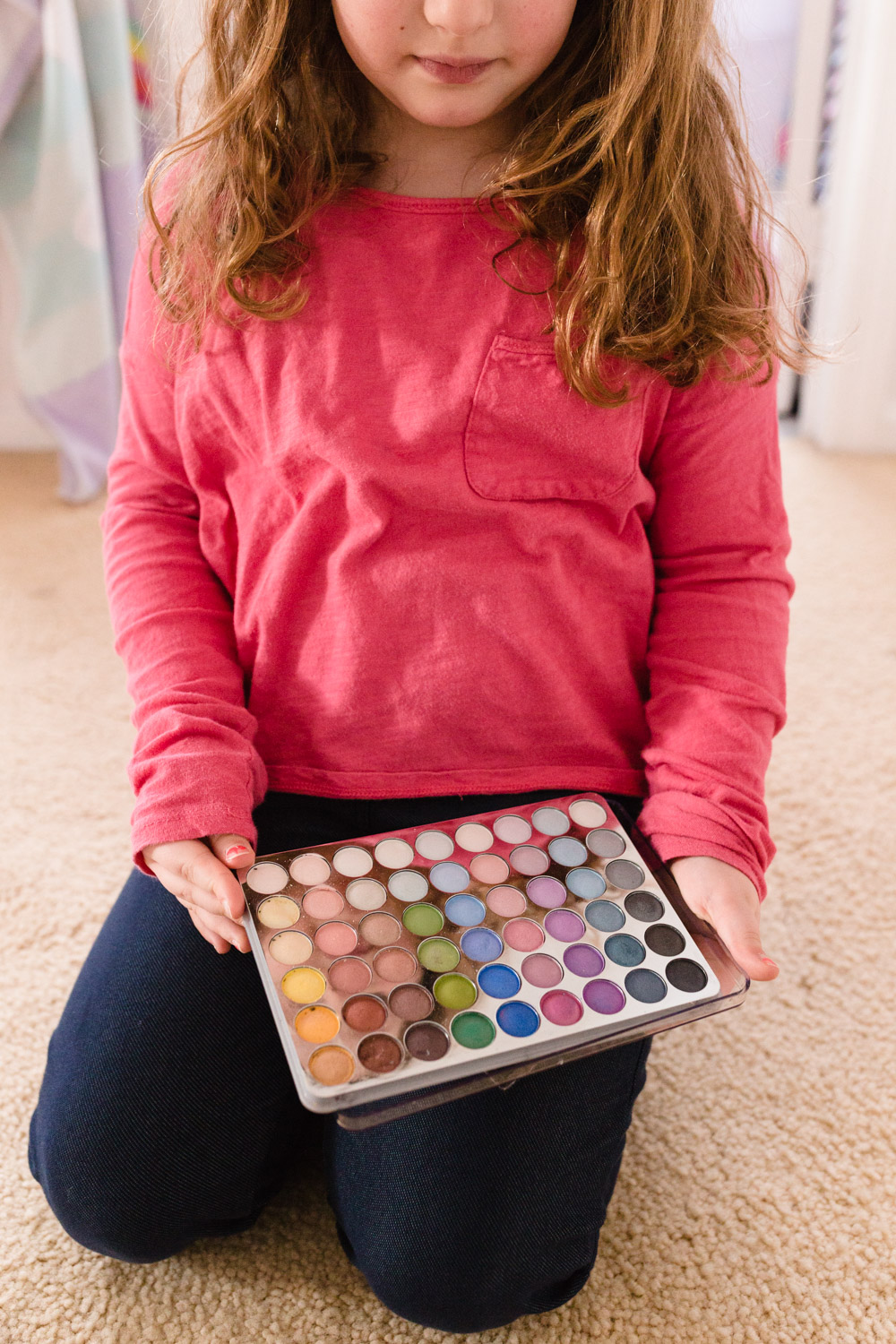 curly haired girl showing me her eye shadow