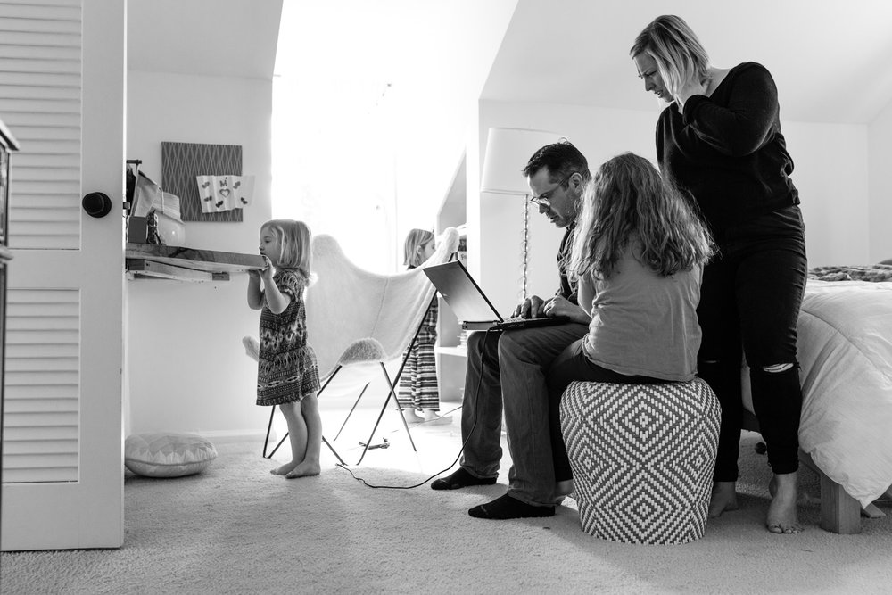family in daughter's bedroom on the computer