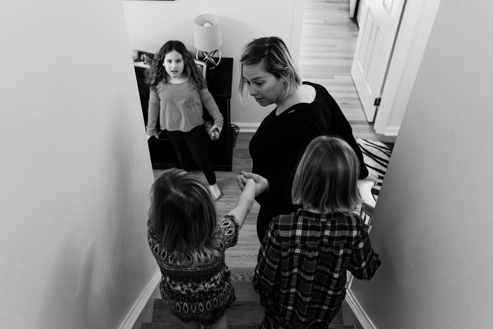 mom and three daughters going downstairs