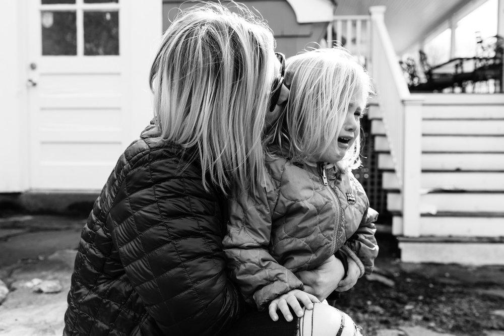 mom comforting toddler daughter