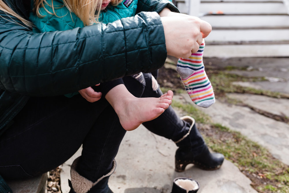 mom putting on a toddler's socks
