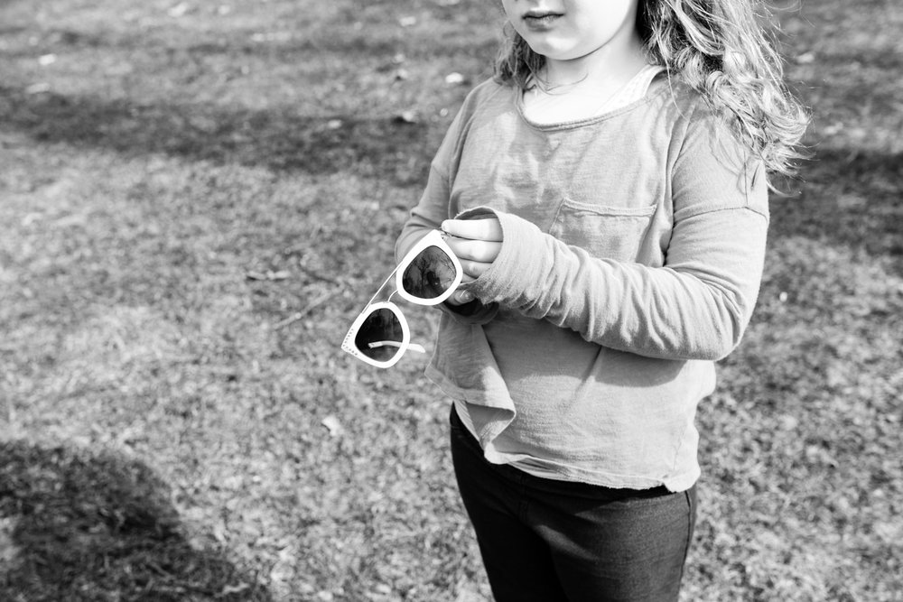 black and white photo of a girl outside with sunglasses