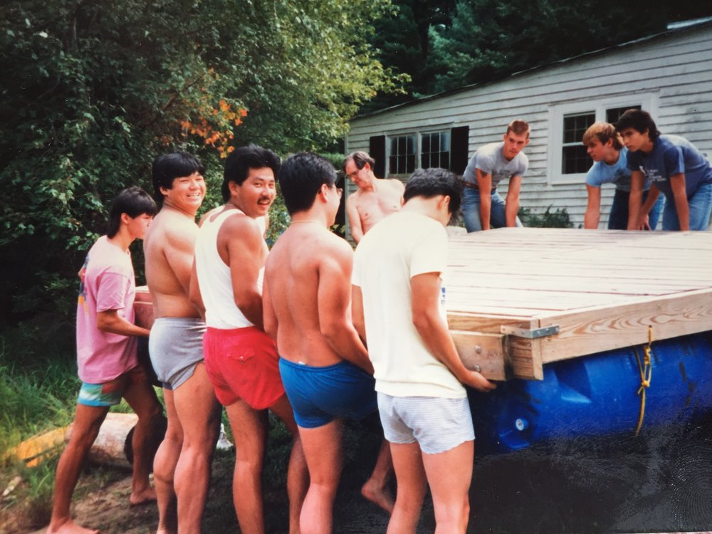 Still Waters hosted groups in the 1970's as a family-owned summer resort. Tao's Dad is in the back with the glasses and Tao is on the right. Guests help with hoisting up the handmade dock.