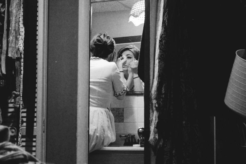 black and white image girl applying makeup