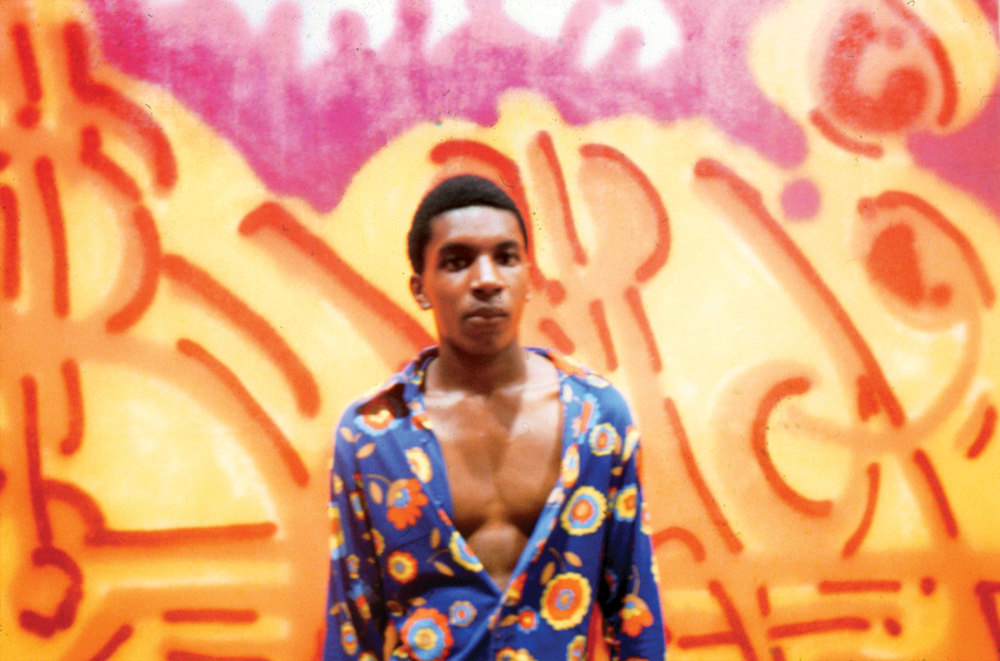"""BAMA poses in front of his painting """"Orange Juice"""" at the Razor Gallery. 1973."""