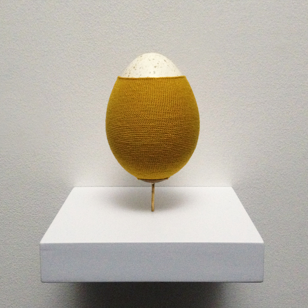 Esther Traugot, Turkey Egg 3, 2015, turkey eggshell, hand-dyed cotton thread, brass mount, wood shelf, 4 x 4 x 4 inches