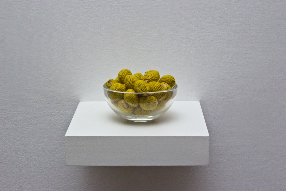 "Esther Traugot, ""Life In A Bowl,"" 2016 cherry pits, dyed cotton thread, small glass bowl, wood shelf, 3 ½ x 3 ½ x 2 inches"