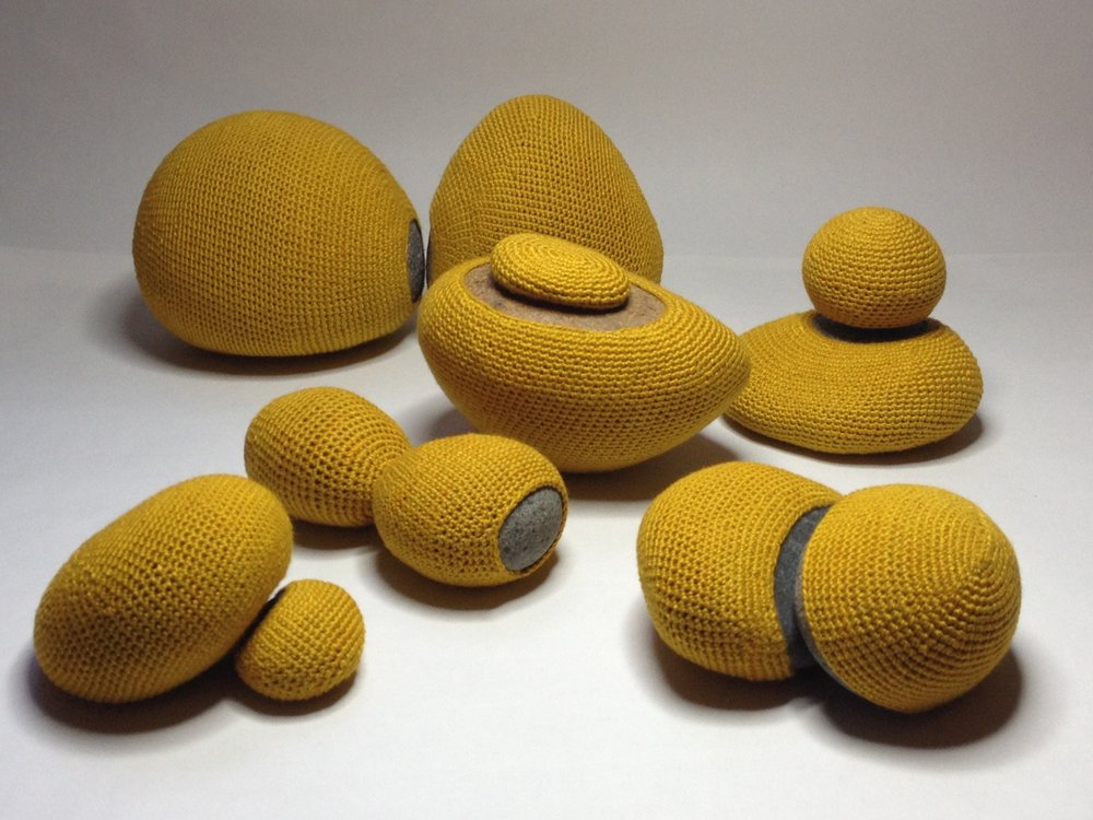 """Esther Traugot, """"River Stones,"""" 2018, pairs of granite stones, dyed cotton/bamboo yarn varying sizes between .5 x 2 inches–3.5 x 5 inches"""