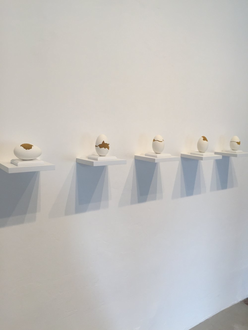 """Esther Traugot, """"Patched Goose Egg #3-#7,"""" 2018, goose egg shell, dyed cotton string, wood mount and shelf, ~4.75 x 6 x 6 inches each"""