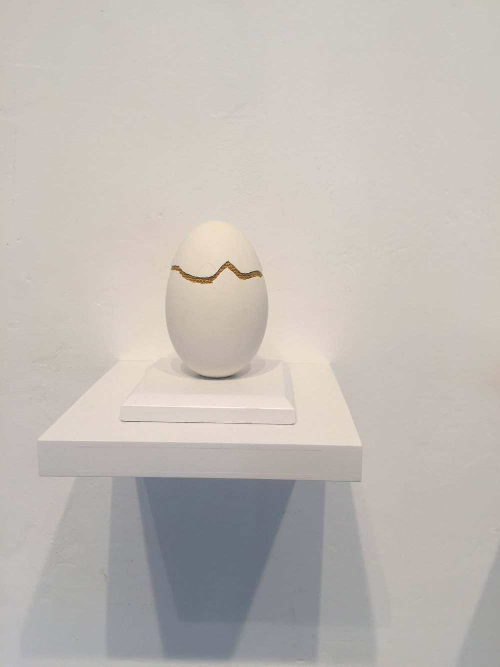 """Esther Traugot, """"Patched Goose Egg #5,"""" 2018, goose egg shell, dyed cotton string, wood mount and shelf, 4.75 x 6 x 6 inches"""