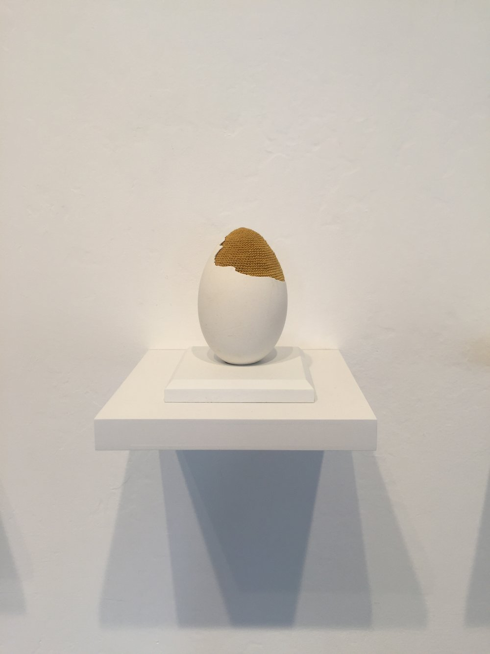 """Esther Traugot, """"Patched Goose Egg #6,"""" 2018, goose egg shell, dyed cotton string, wood mount and shelf, 4.75 x 6 x 6 inches"""