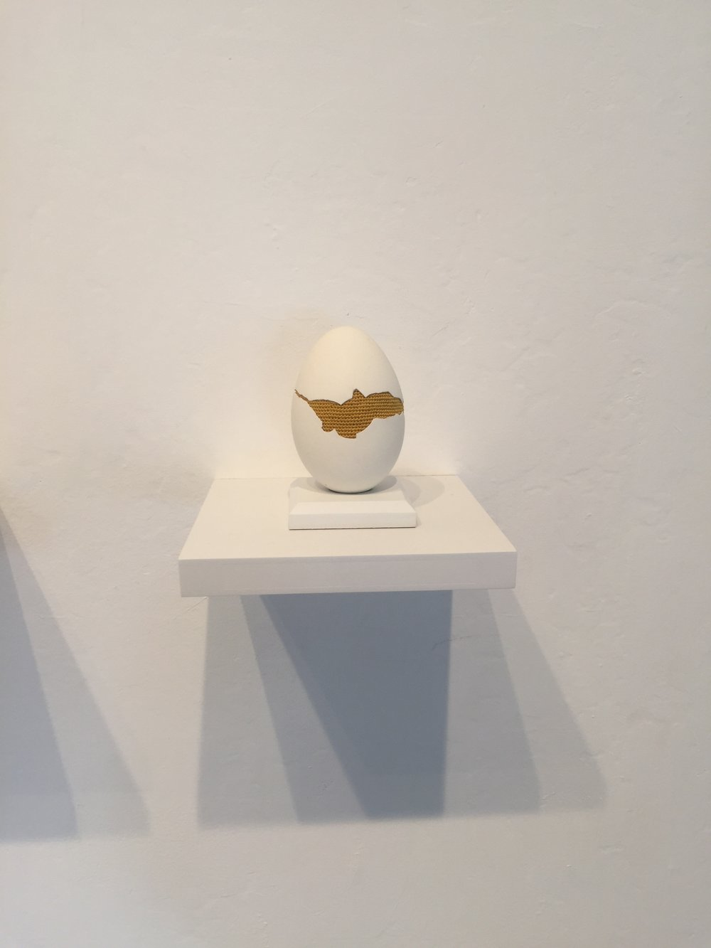 """Esther Traugot, """"Patched Goose Egg #7,"""" 2018, goose egg shell, dyed cotton string, wood mount and shelf, 4.75 x 6 x 6 inches"""