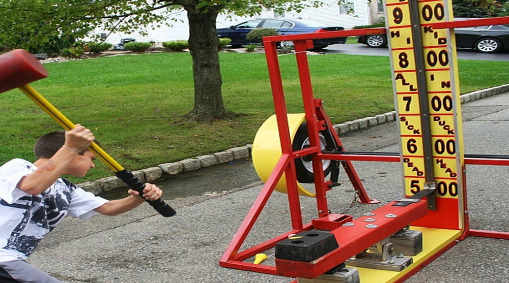 Test-O-Strength - A high striker operates by utilizing the lever where one end holds a puck attached to the tower and the other end is struck by the person or contestant using a hammer or mallet.