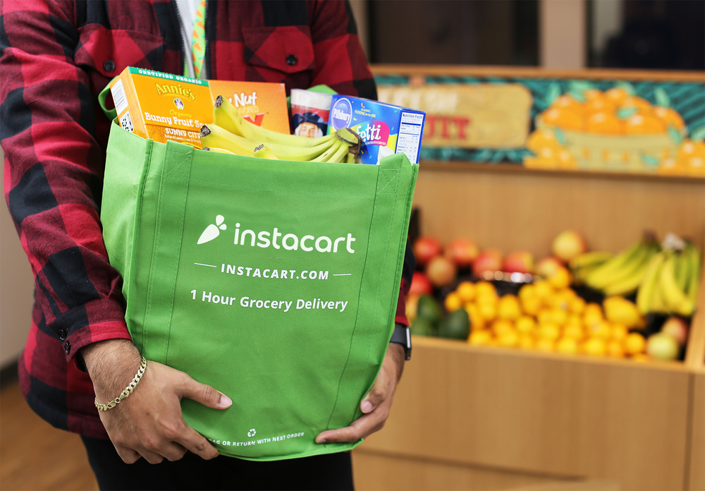 Man holding a full instacart reusable bag, with produce in the background