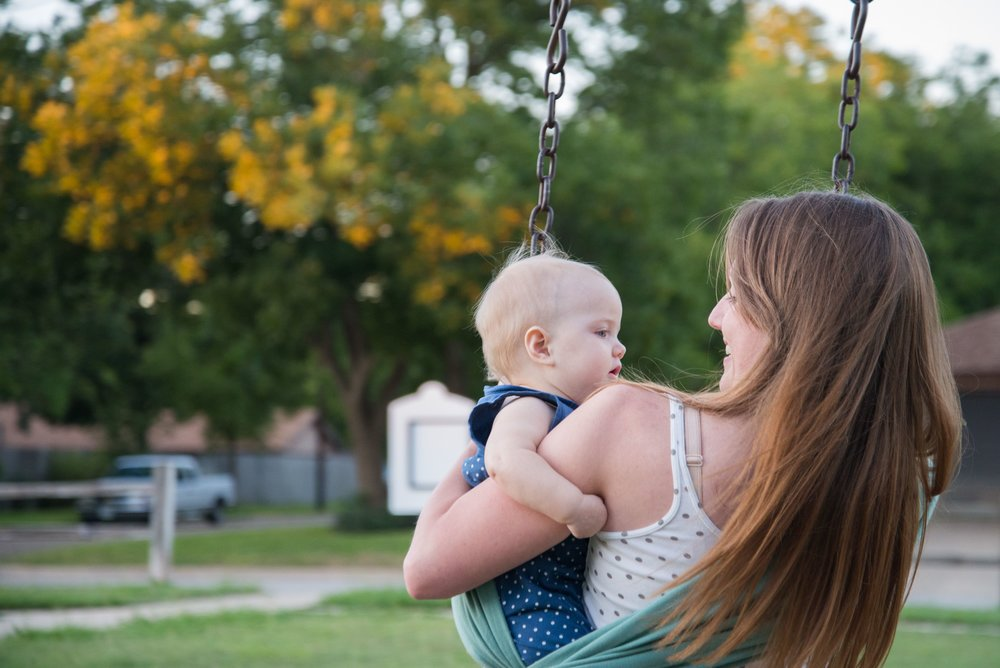 Nursing mom sits on swing holding baby Capitol Hill preparing for breastfeeding