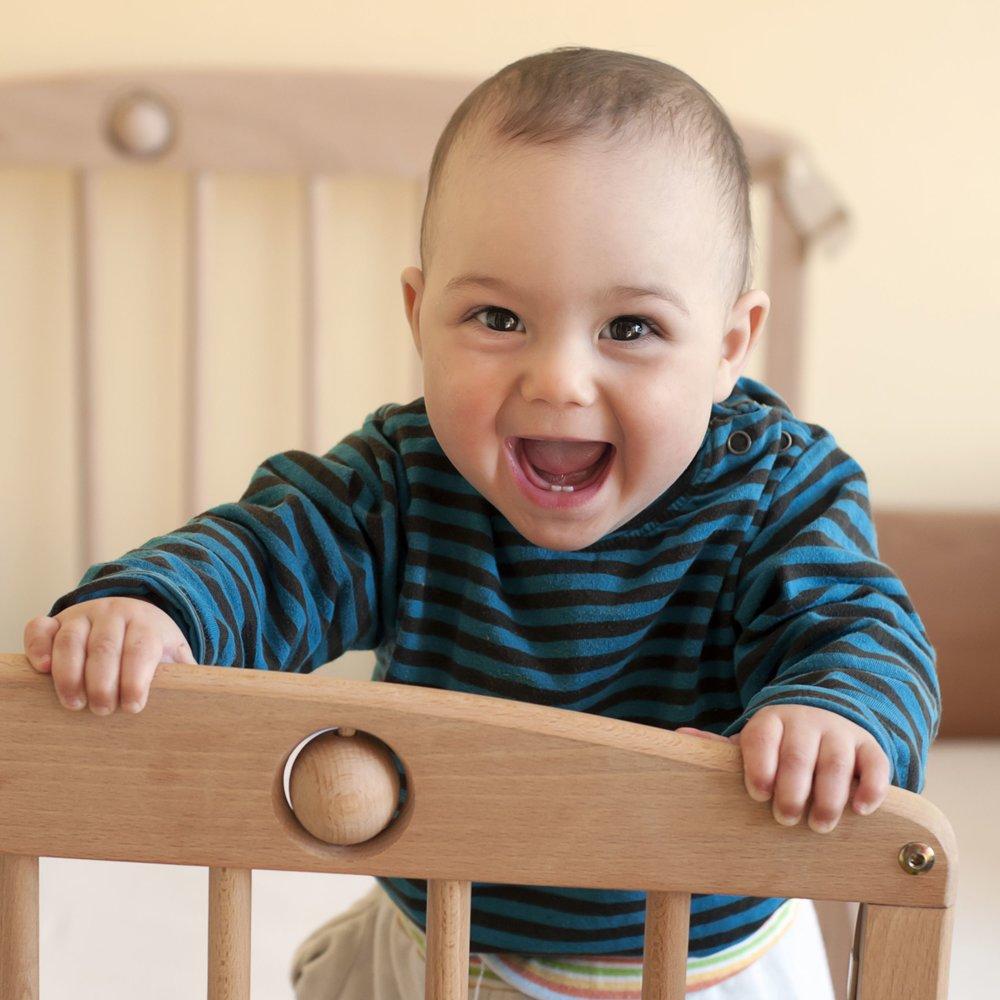 Smiling baby in crib Washington DC sleep support
