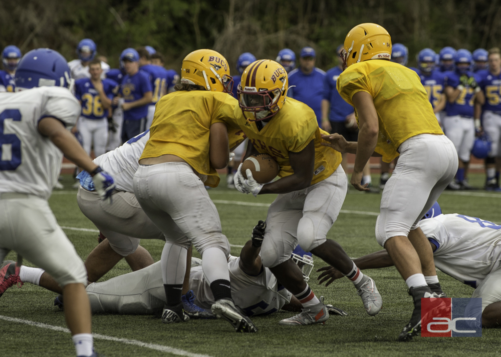 Kingston senior Alex Barrett drives through Olympic's defense during a practice scrimmage Friday, August 28, at Kingston High School. Bainbridge Island also participated in the pre-season jamboree.