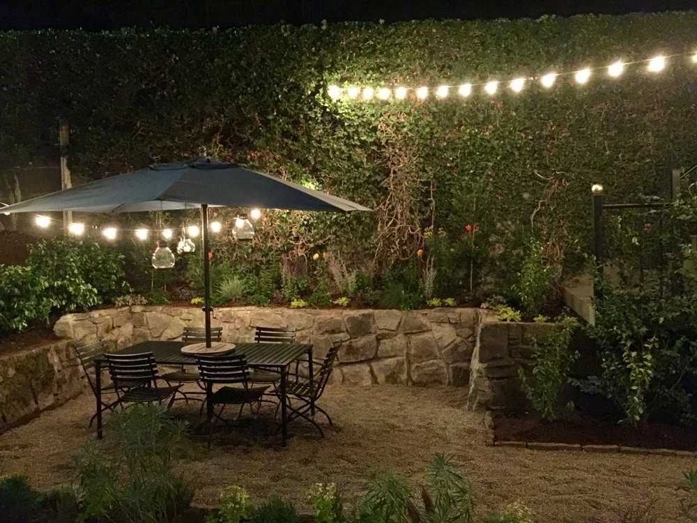 Classic outdoor eating area. Ivy hedge with thick foliage surround the patio. Pea gravel patio. Daniel House.