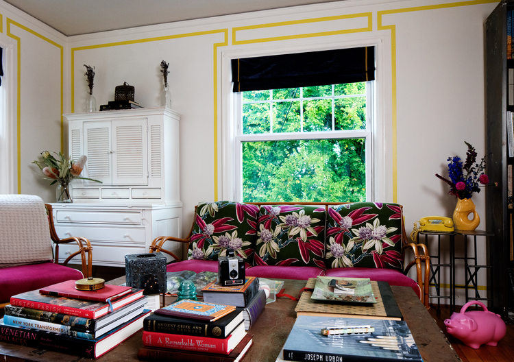 Bright living room. Ratan couch with Hawaiian upholstery. Outlined walls. Traditional interior design.