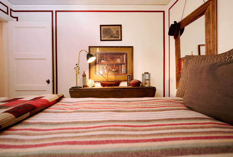 Cozy bedroom with masculine tones. 1940's wooden ship. Striped blanket. Daniel House.