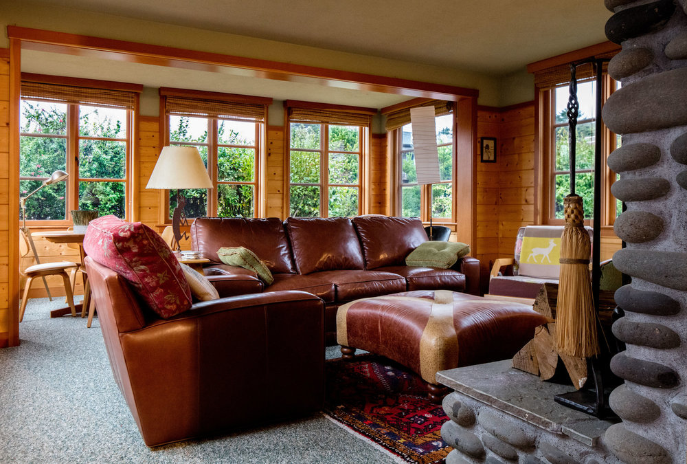 Comfortable living room in Oregon beach house. Stone fireplace. Leather couches. Wood walls. Daniel House
