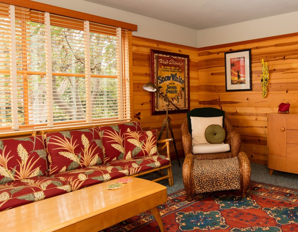 Wood walled family room in Oregon beach house. Ratan couch in Hawaiian upholstery. Classic Cabin design. Daniel House.