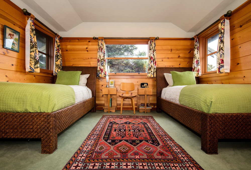 Twin beds in a cabin bedroom, Pine walls with wicker furniture and Persian rug. Traditional cabin. Daniel House.