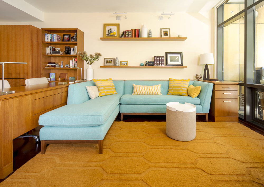 Orange carpet with blue Jonathan adler couch. Custom desk wraps around couch. Portland modern design. Daniel House.