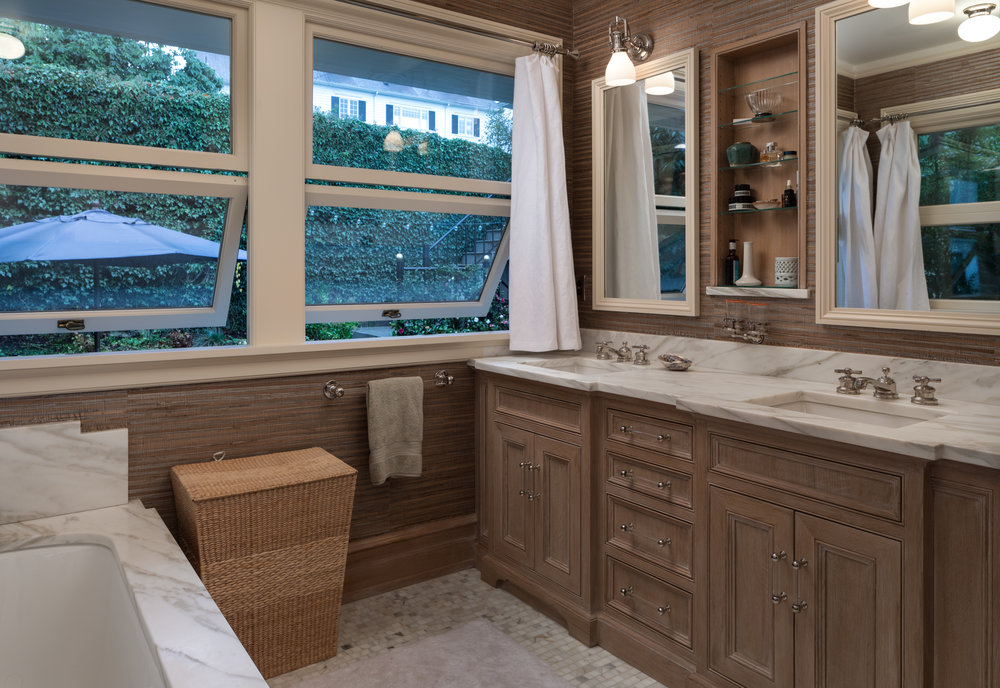Limed wood, grass cloth, and marble create an atmosphere of sophistication in this master bath.