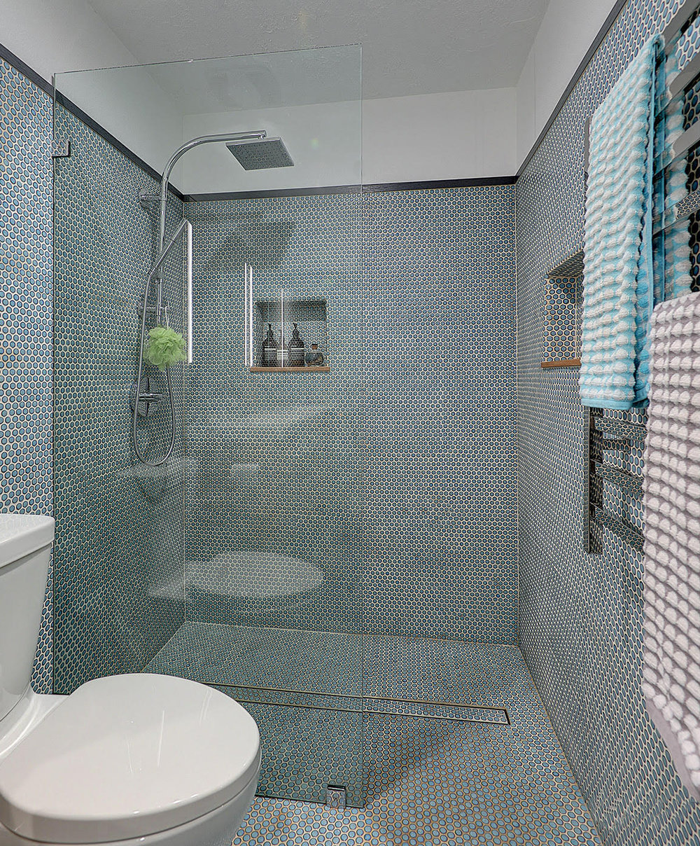 a modern bathroom design using penny tile on the floors and wall.