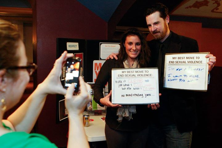 "Two people are posing for a photo while a third person takes a picture on their phone. The two people are holding whiteboards. One reads ""My best move to end sexual violence: Make it CLEAR not just what I DON'T want but also what I DO want. No mind reading junk."" The other says ""My best move to end sexual violence: I want to hear what you want."""