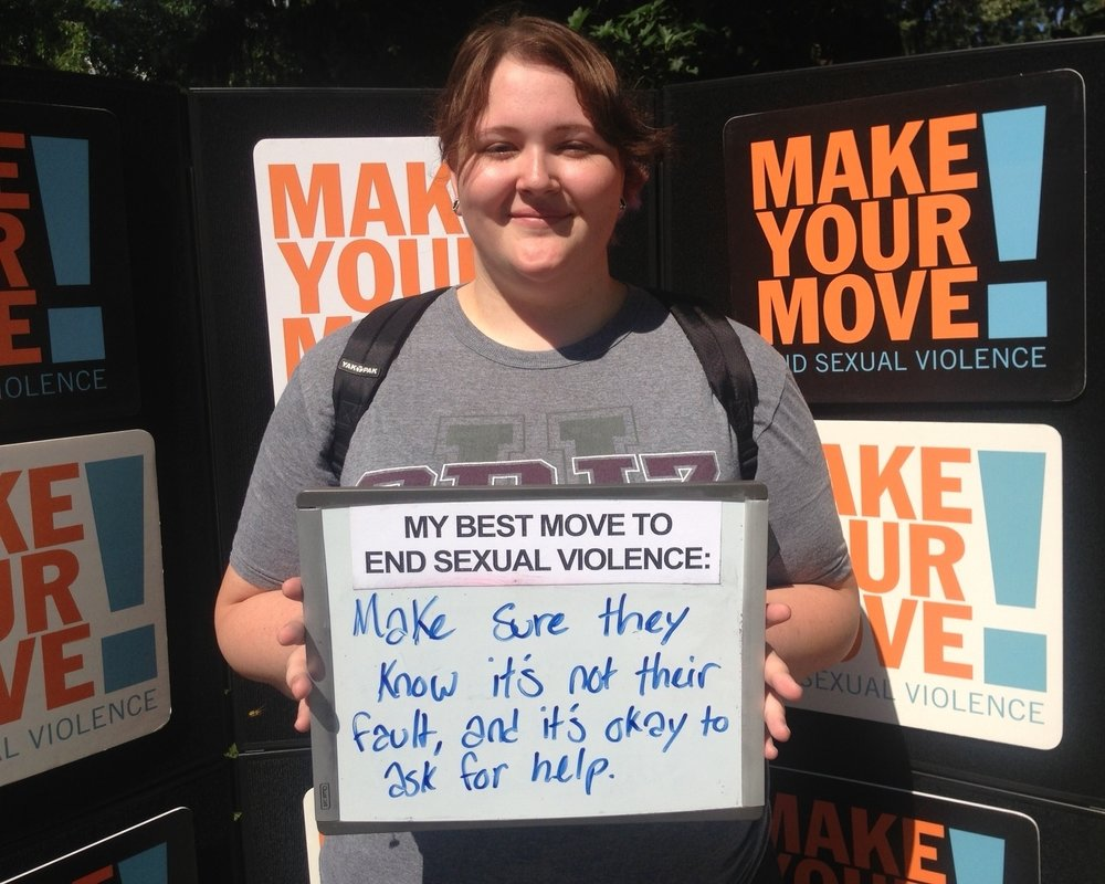 "A person with brown hair holds a whiteboard. The sign says: ""My best move to end sexual violence: Make sure they know it's not their fault, and it's okay to ask for help."""