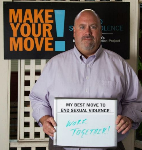 "A man stands in from of a Make Your Move! sign. He is holding a whiteboard that reads ""My best move to end sexual violence: Work Together!"""