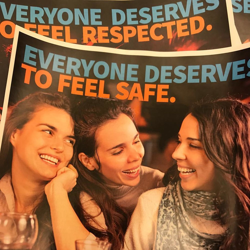 "A pile of patron posters show three women at a bar laughing together. The header reads ""Everyone deserves to feel safe."""