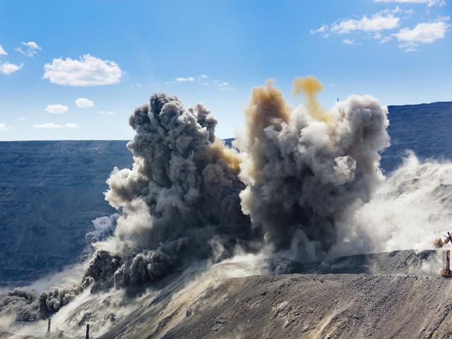 A blasting operation's sequence of explosions propels dirt and rocks upward in an open cast mining quarry.