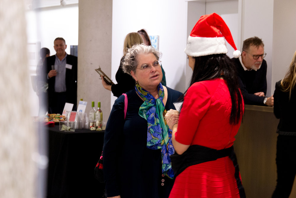 Eileen Kaminsky entertains festive guests during her holiday fundraiser at C24 Gallery.