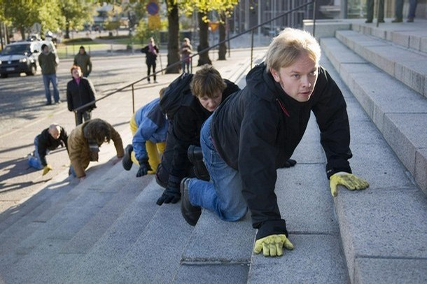 Five persons belonging to a performance group crawl up to the parliament building in Helsinki