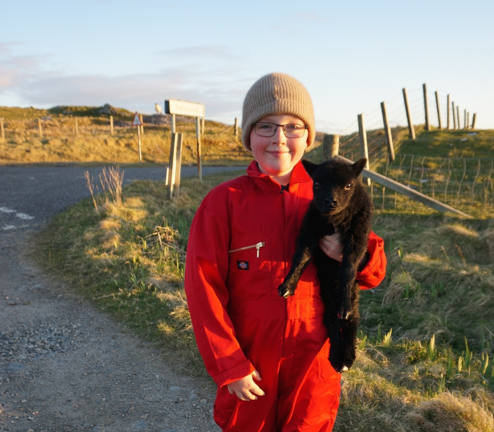 A wee crofter with a wee lamb needing a little extra help along the road.