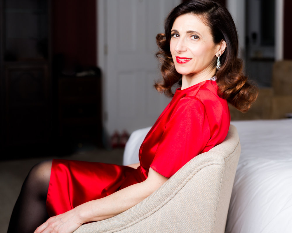 Portrait of a woman with a satin red dress and glamour hairstyle, celebrating her 50th birthday.Celebrate your birthday in style. Turning 50 is a milestones, make it something special, celebrate it with a photoshoot to remember.  Sonia choose to make her portrait story about the Cannes Film Festival. Read about Sonia's photoshoot on the  blog