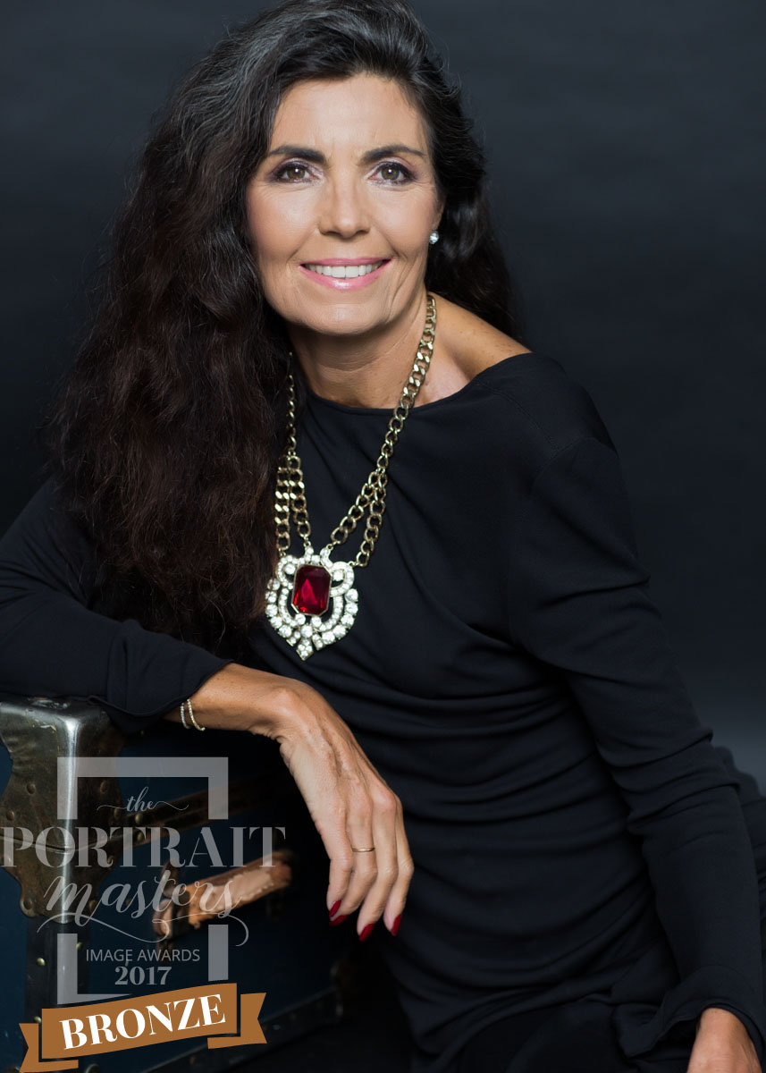 Portrait of a woman over 60 with long hair, shot in the studio wearing a navy dress and a statement necklace. Elegance has no age. A timeless and elegant portrait that celebrates the women you are a women who embraces being over 60. This portrait was awarded bronze at the portrait masters accreditation awards.