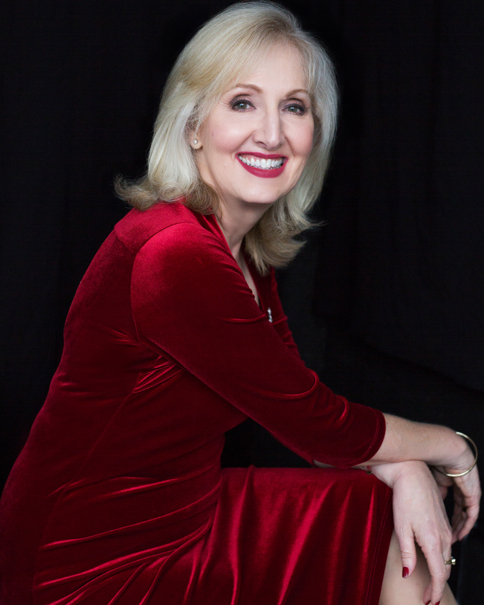 Portrait of a woman over 60, celebrating her style in a gorgeous red dress. When red is your colour. Barbara is a clothes stylist, she knows what will suit you and will help make the first impression lasting.