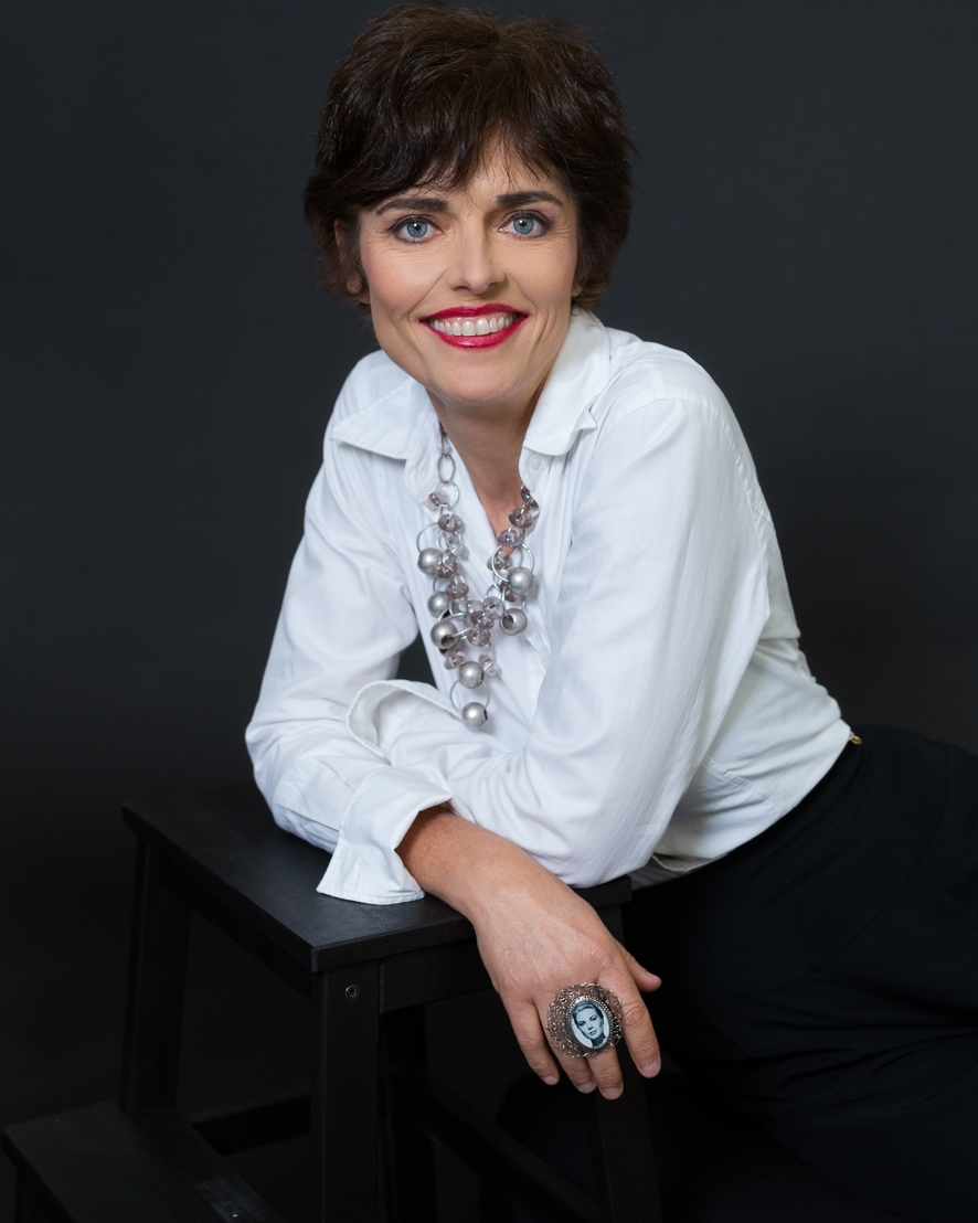 Parisian Chic styling for a Portrait of a woman over 50 wearing short hair, red lipstick a white shirt, a statement necklace and chunky ring, Shot in the studio.  When teaching French, Embrace your inner Parisian!