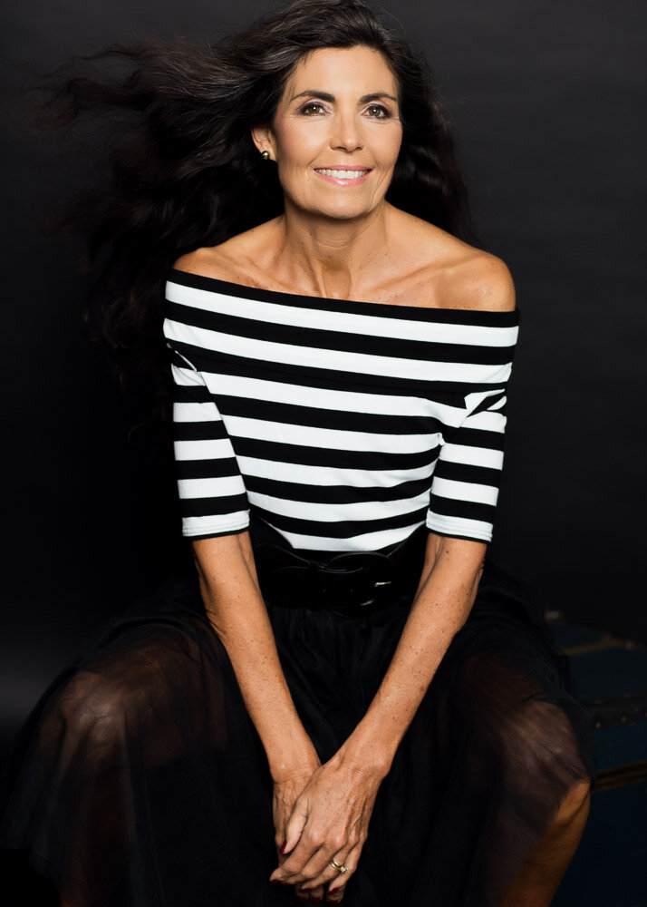 Portrait of a woman over 60, wearing long hair, a black tulle skirt and a bardot stripy top. Rock your inner French. Reconnect with the woman you've always been! Rock your inner Parisian with a glam breton top.